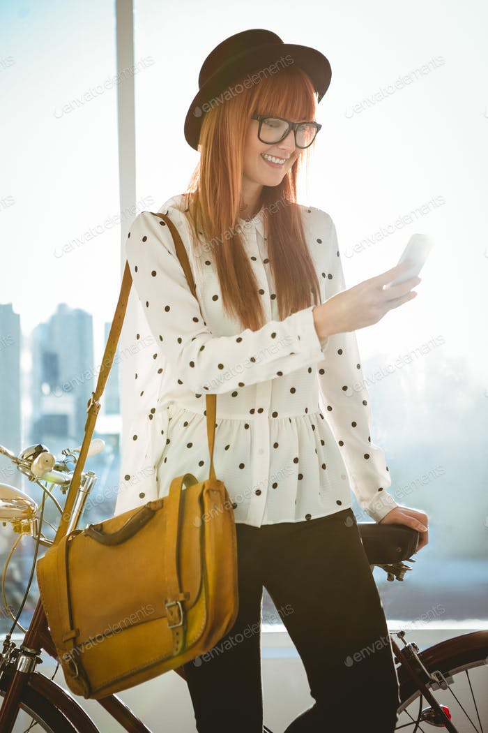Smiling hipster woman taking selfie in a bright room