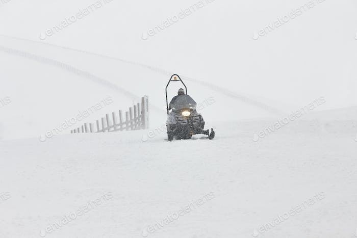 Snowmobile on the snow. White winter mountain landscape. Horizontal