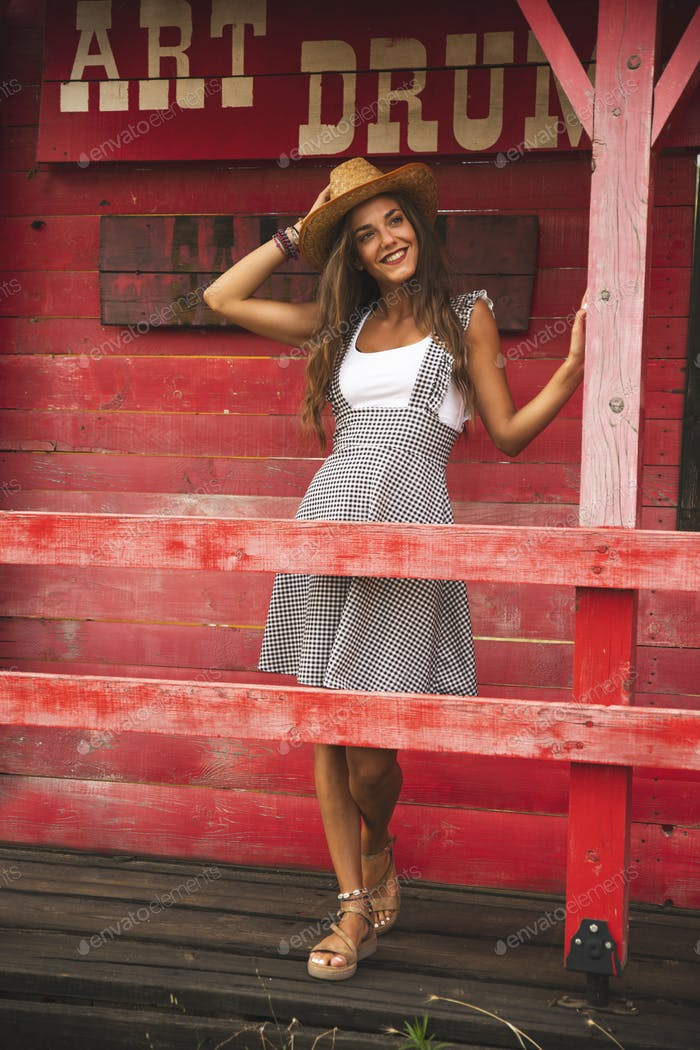 Beautiful Girl Posing Outside at a wooden Red Saloon Bar
