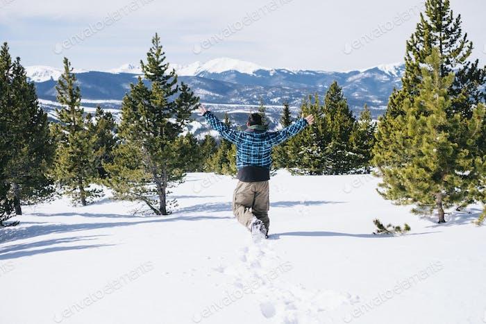 Ein Mann, der durch Tiefschnee auf einem Berghang läuft.