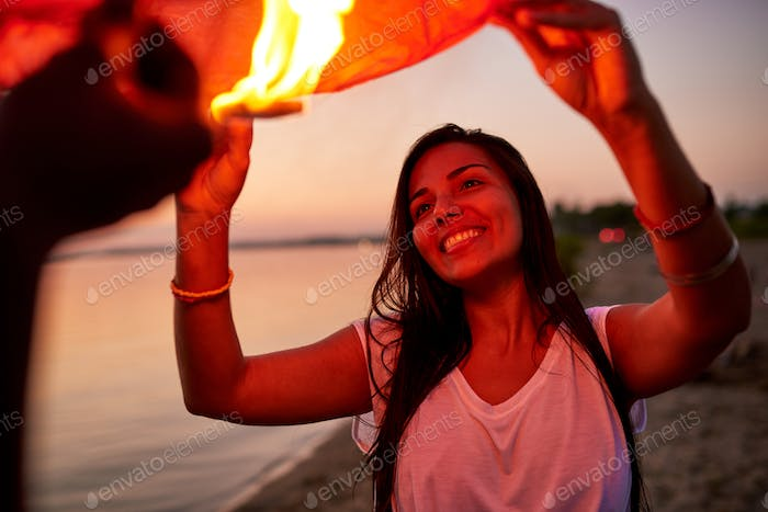 Happy pretty girl holding sky lantern with friend