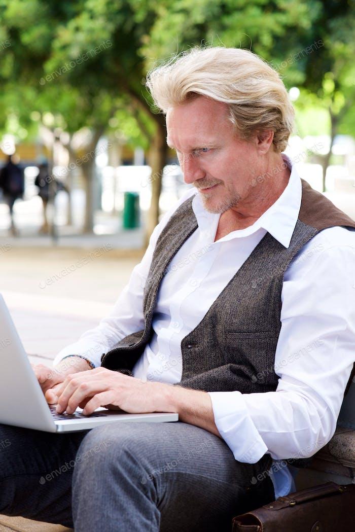 mittleren Alters Mann sitzen draußen mit Laptop