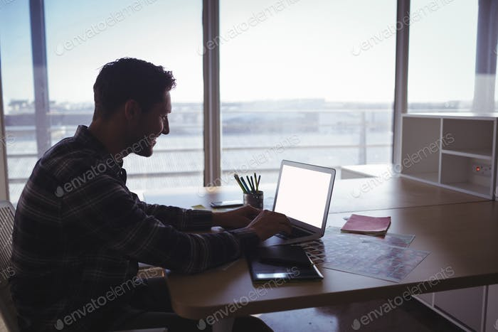 Young businessman using laptop on desk in office