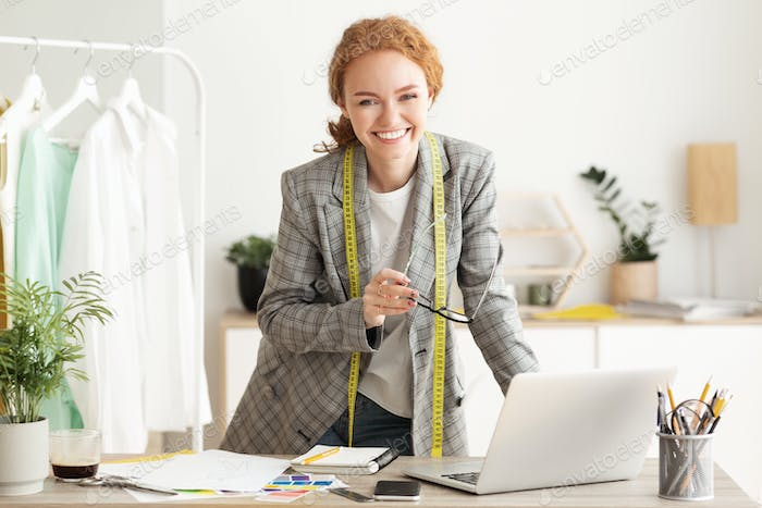 Happy designer woman work on computer in tailor workshop