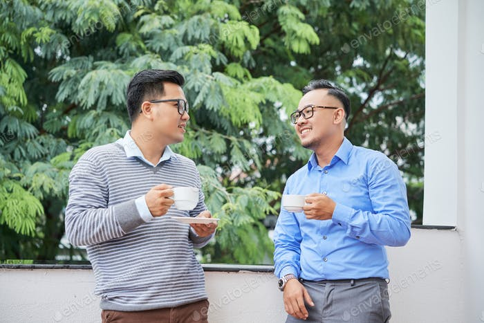 Talking young ethnic men with coffee outdoors