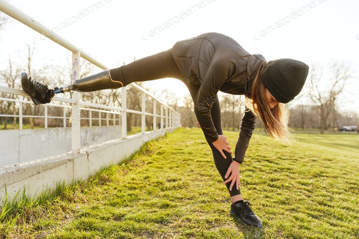 Photo of disabled running woman in sportswear, doing slopes and