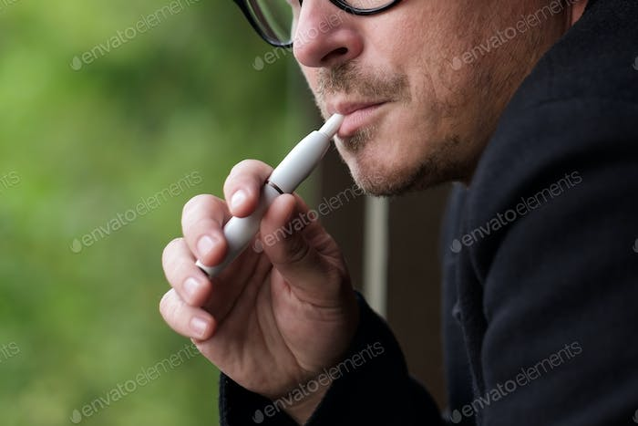 Caucasian man smoking modern hybrid cigarette device outdoor