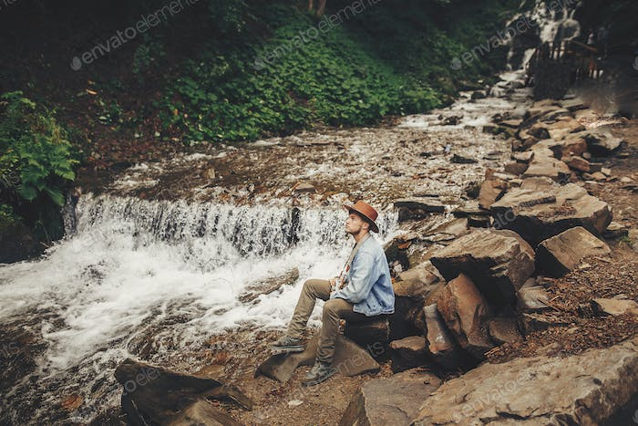 stylish hipster man in hat with photo camera,sitting at river with waterfall in forest