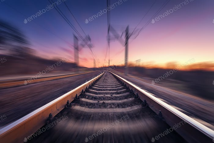 Railway station at colorful sunset with motion blur effect. Rail