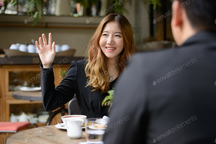 Happy young Asian business couple together at the coffee shop