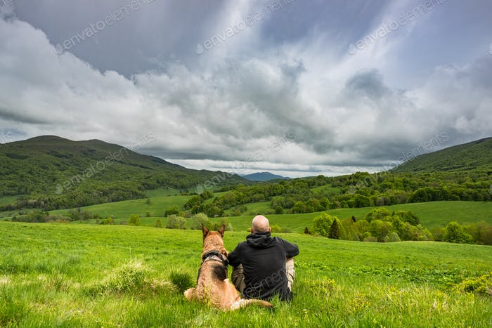 Active man sitting with dog in mountains, looking at view ad res