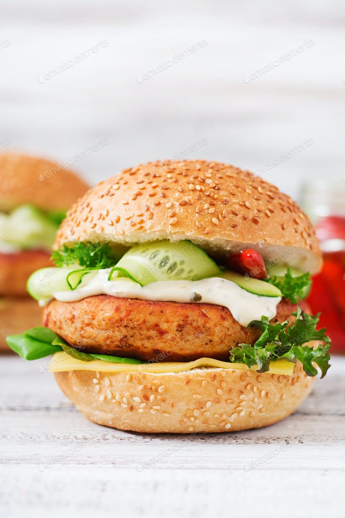 Big sandwich - hamburger with juicy chicken on a light wooden background