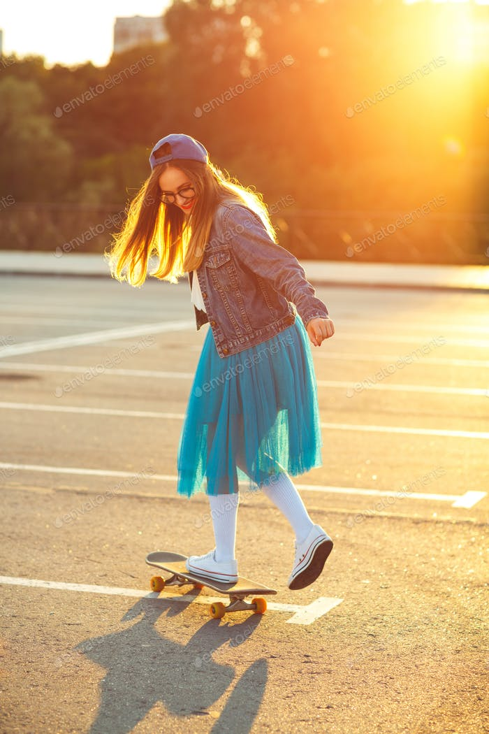 Beautiful young woman with skateboard, backlit at sunset