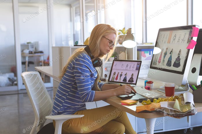 Young female fashion designer using graphic tablet at desk in a modern office