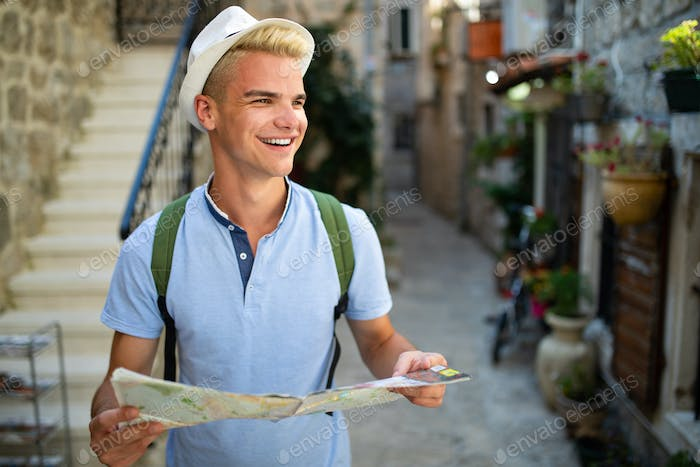 Happy young tourist man having fun and travelling on summer vacation