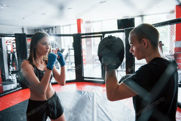 Athletic young people have sparring on the boxing ring