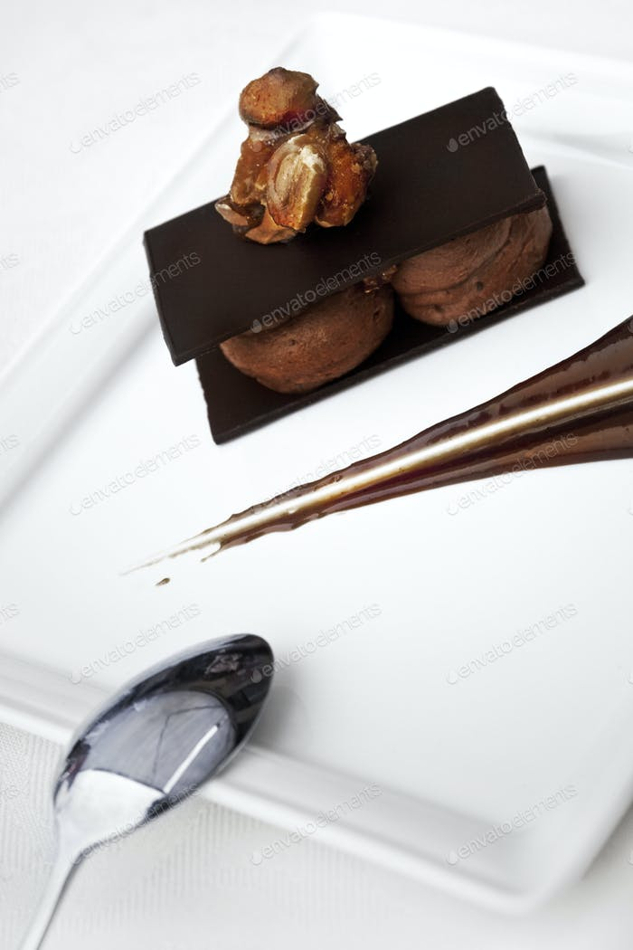Chocolate dessert and spoon on a white plate