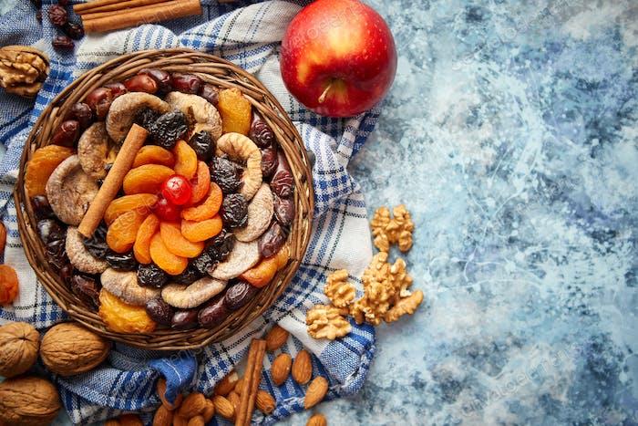 Zusammensetzung von getrockneten Früchten und Nüssen in kleinen Weidenschale auf Steintisch platziert
