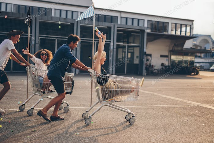 Young friends racing with shopping carts