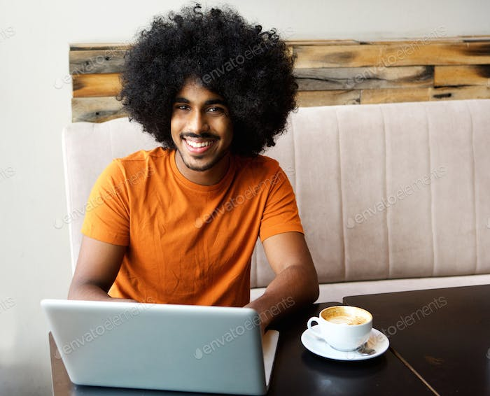 Smiling young black man with laptop on cafe table