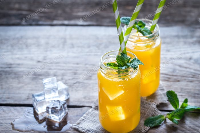 Glass jars of orange juice with ice