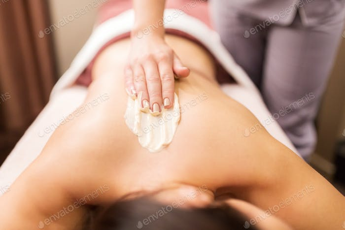 woman having back massage with cream at spa