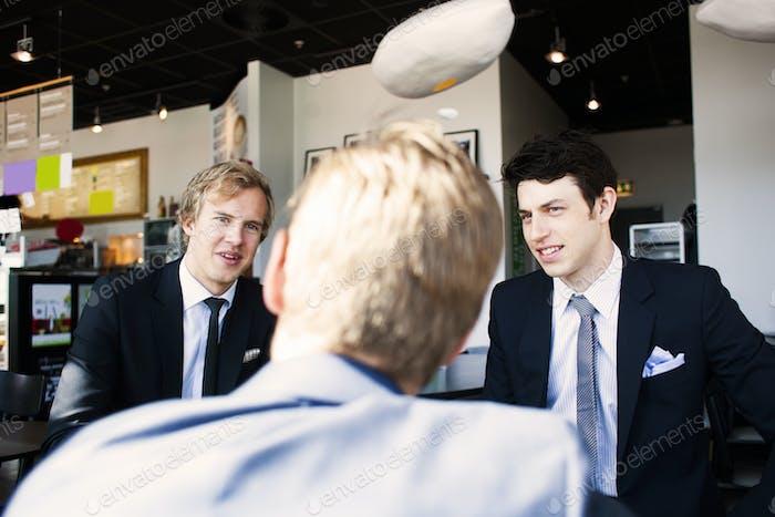 Бизнесмены обсуждают с коллегой в кафе