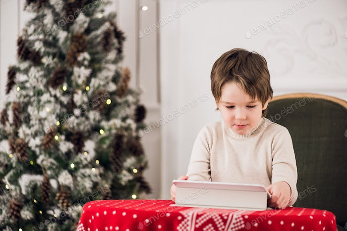 Portrait of cute kid boy sitting on green chair and playing with computer tablet during Christmas