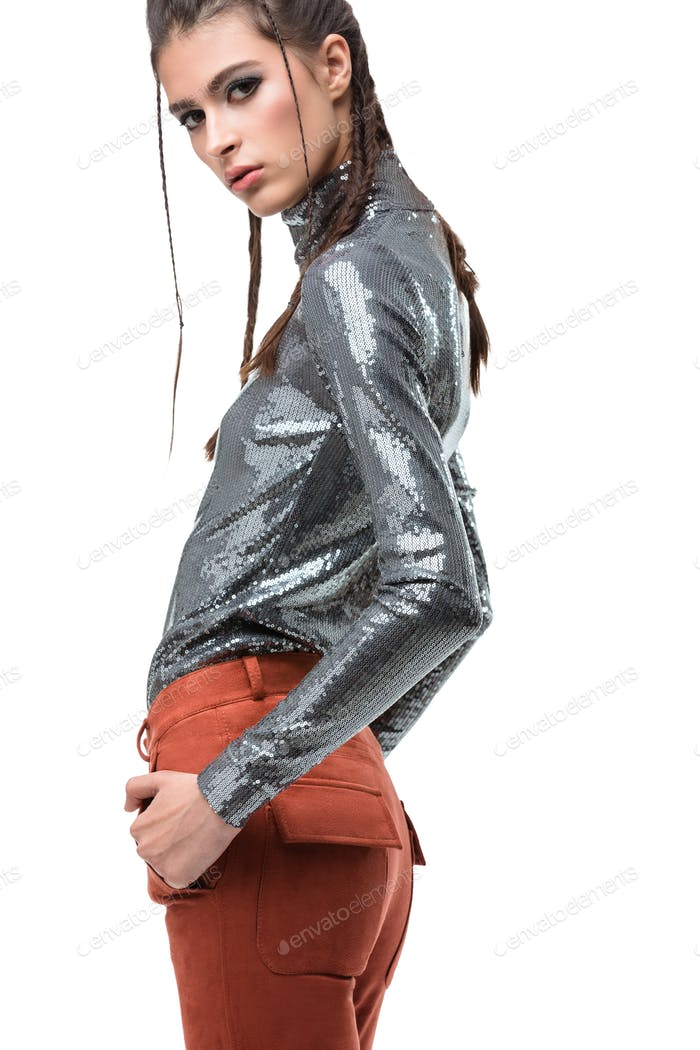 Portrait of beautiful lady standing in light brown suede trousers and silver top with sequins