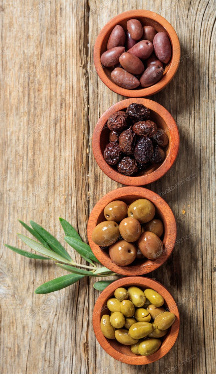 Olives variety in wooden bowls, wood table, top view