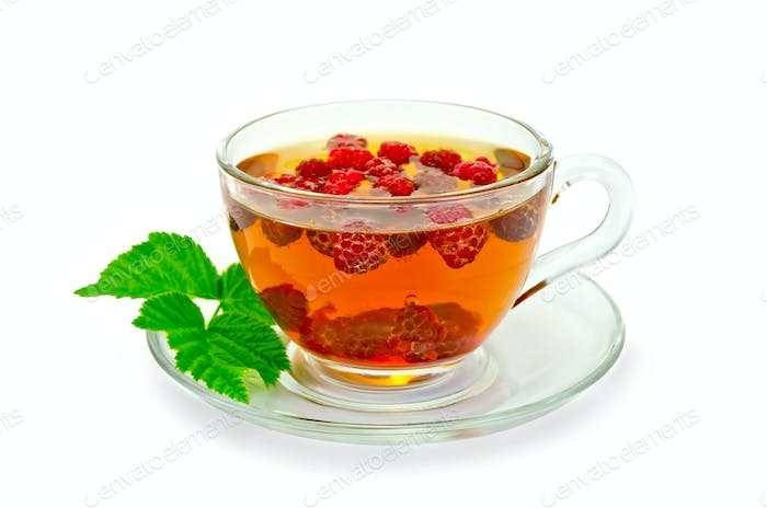 Tea with raspberries and a leaf in a cup