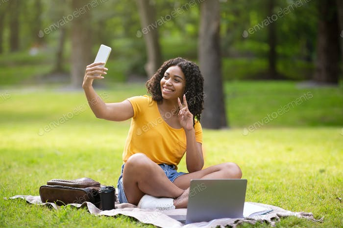 Funky black girl with laptop taking selfie while studying at park