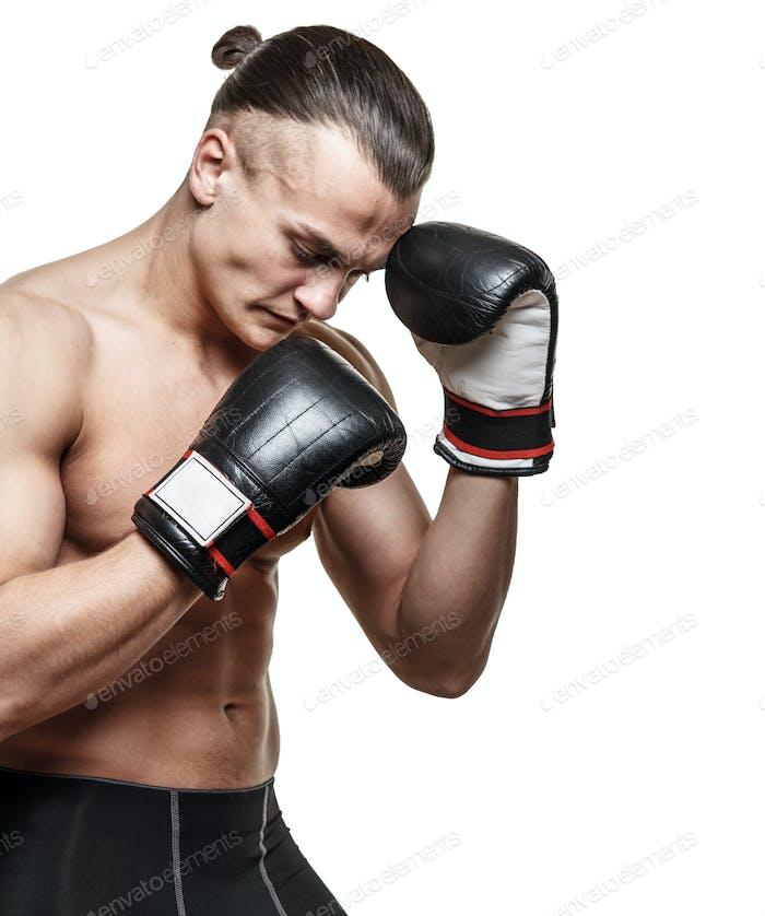 Fighter in boxer gloves posing in studio
