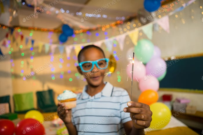 Cute boy holding sparkler and cupcake during birthday party