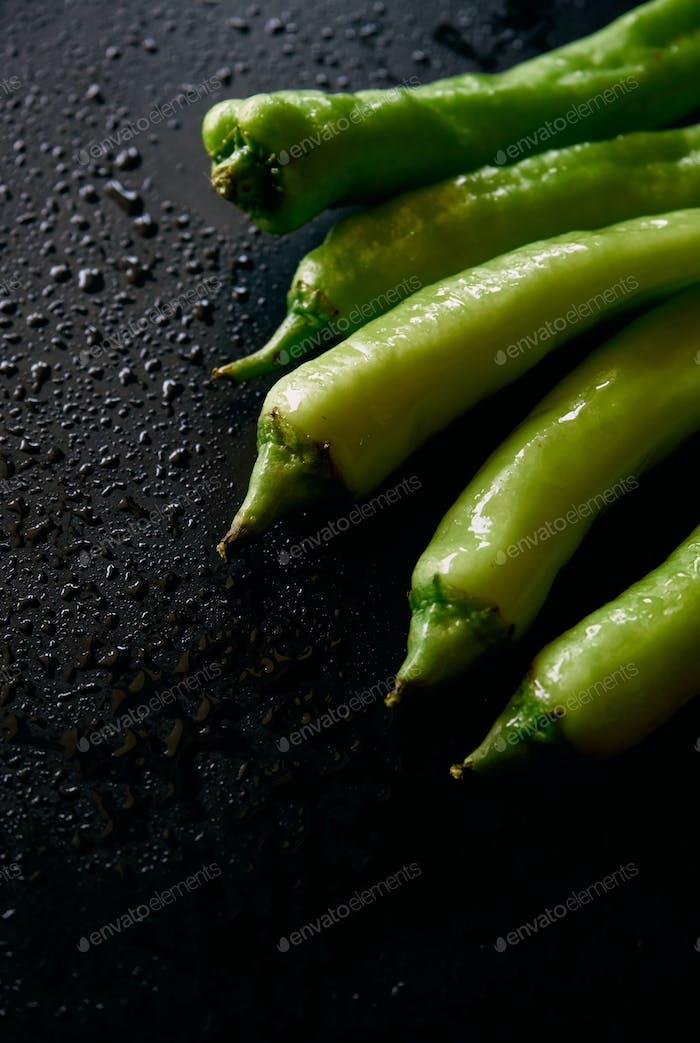 Green chili pepper on the black floor