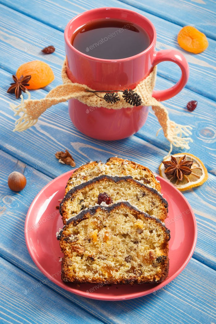 Cup of tea and fresh baked fruitcake on plate