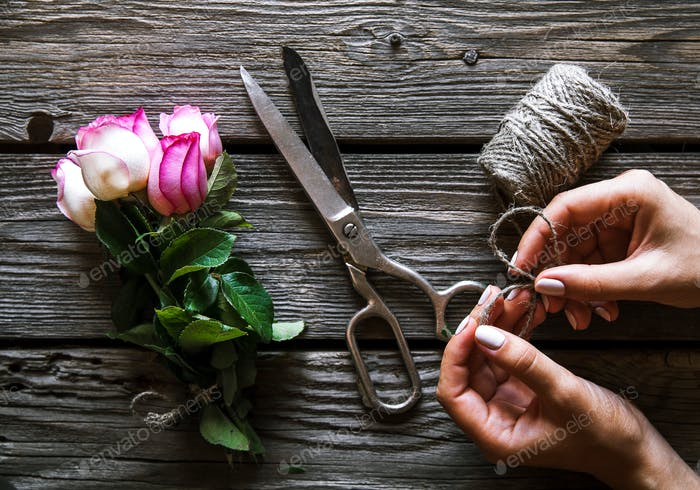 Female hands making the bouquet on wooden table with rose. flowers
