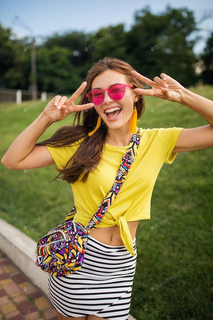 young stylish woman having fun in city park, summer style fashion trend