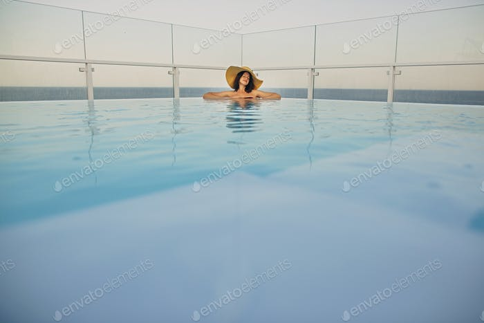 Girl in sunhat on vacation in luxury tropical resort, swimming in pool on rooftop