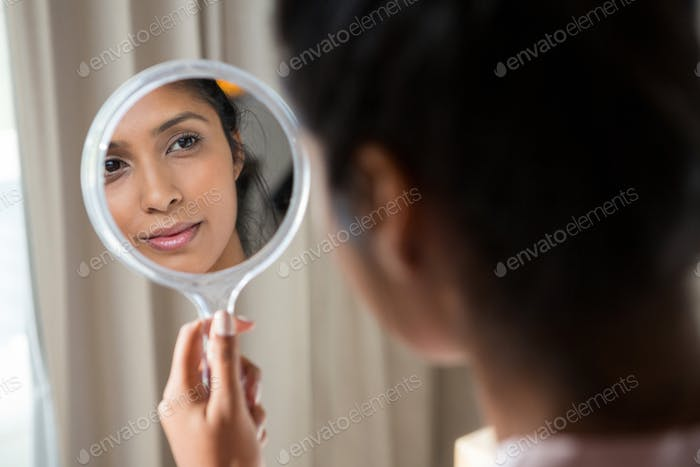 Woman reflecting on hand mirror