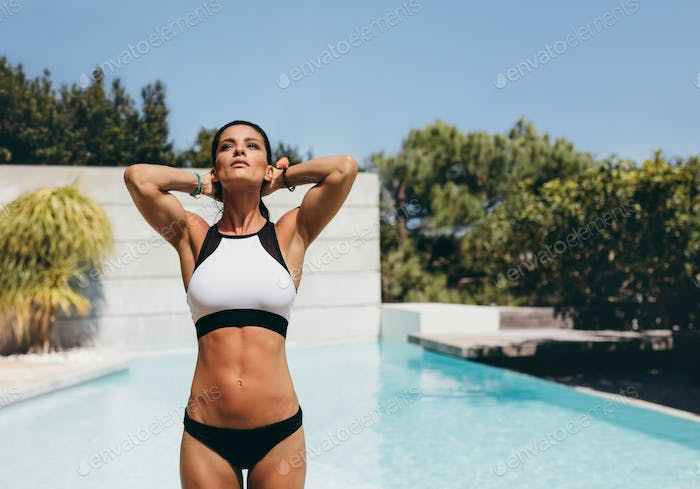 Beautiful young woman posing in a bikini next to a pool