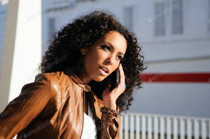 Portrait of pretty blak woman in urban background talking on pho