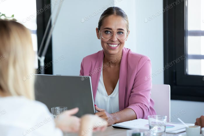Smiling young business woman listening her partner while working with laptop on coworking space.