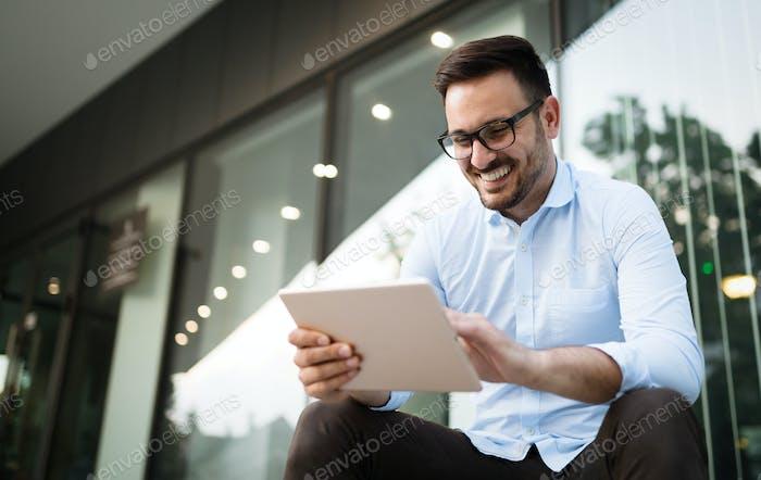 Geschäftsmann trägt eine Brille halten Tablette und lächelnd