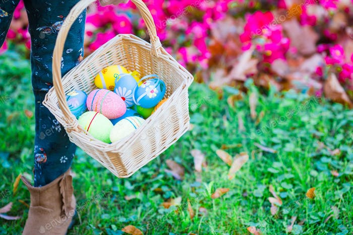 Closeup basket full of colorful Easter eggs in kids hands