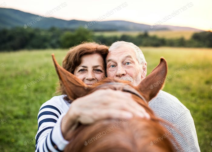 A crazy senior couple standing by a horse outside in nature, looking over his head.