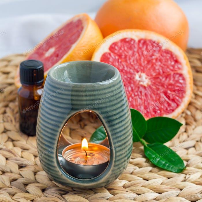 Aromalampe mit Grapefruitöl auf gewebter Matte, Grapefruits auf Hintergrund, quadratisches Format