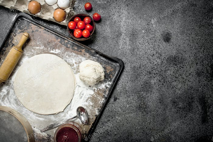 Roll up dough with ingredients for pizza.