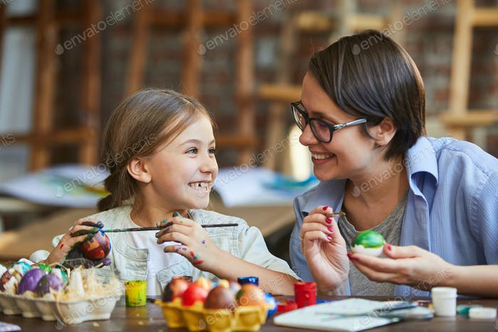 Little Girl Painting Easter Eggs with Mom