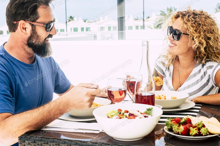 Happy mature adult caucasian couple enjoy lunch together  outdoor